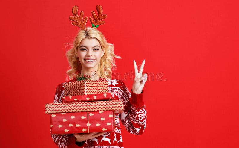 Happy young cheerful girl laughs and jumps in christmas hat and with  gift on  red   background stock photography