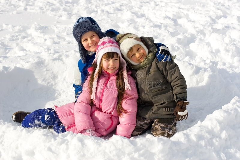 Happy Young Children On Snow. Portrait of sister and two brothers on snow stock photography
