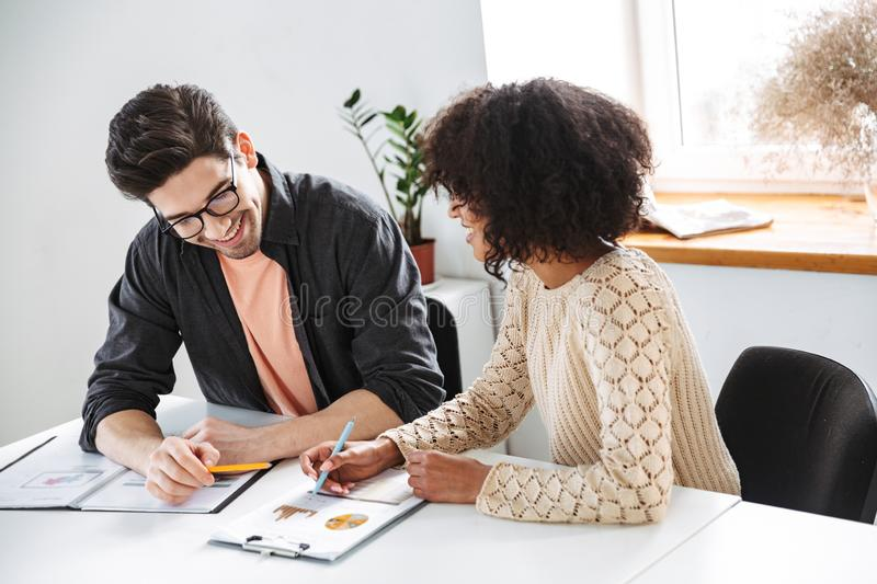 Happy young colleagues having fun together and reading documents. While sitting by the table at office stock image