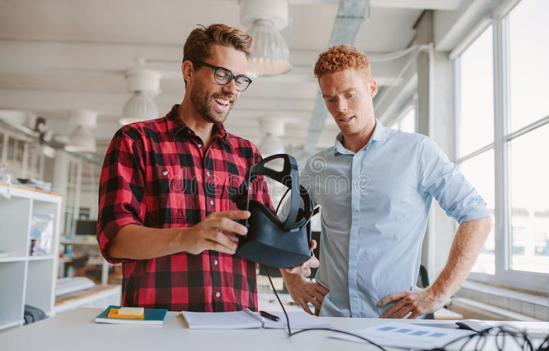 Happy young colleagues working on virtual reality device. Shot of happy young men testing virtual reality goggles in office. Business colleagues working at desk stock images