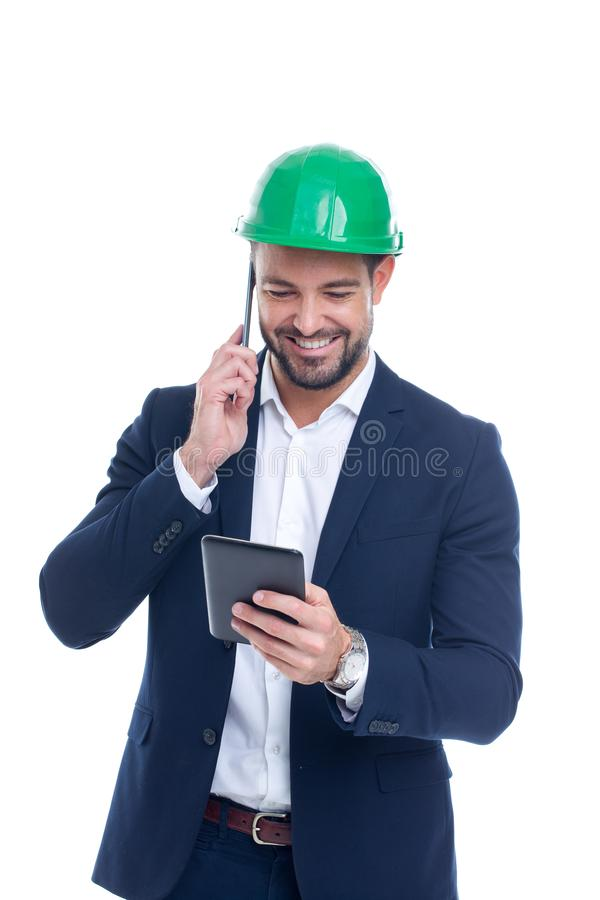 Happy young construction manager calling and using tablet isolated royalty free stock image