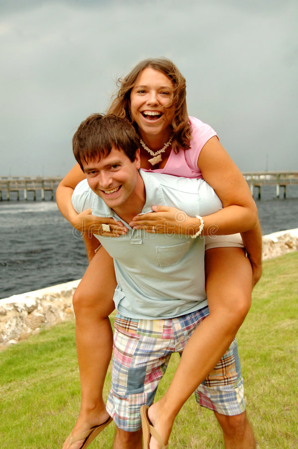 Happy young couple. A happy young playful couple piggyback in a park by the water stock photo