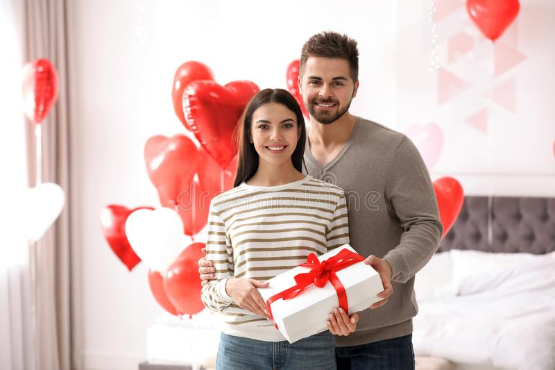 Happy young couple in bedroom decorated with heart balloons. Valentine`s day celebration. Happy young couple in bedroom decorated with heart shaped balloons royalty free stock photos