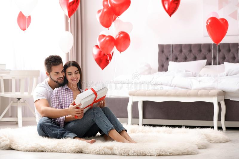 Happy young couple in bedroom decorated with heart balloons. Valentine`s day celebration. Happy young couple in bedroom decorated with heart shaped balloons royalty free stock photo