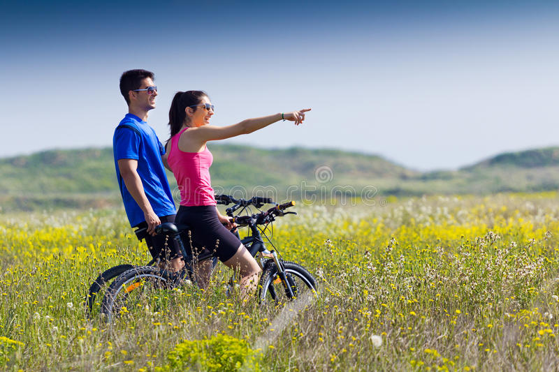 Happy young couple on a bike ride in the countryside stock images