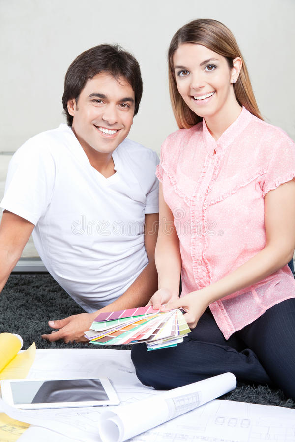 Happy Young Couple with Blueprints and Color stock image