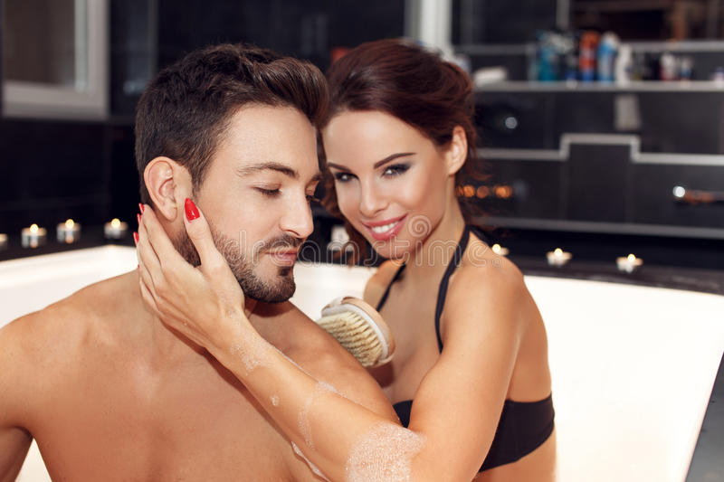 Happy young couple with brush in jacuzzi royalty free stock photography