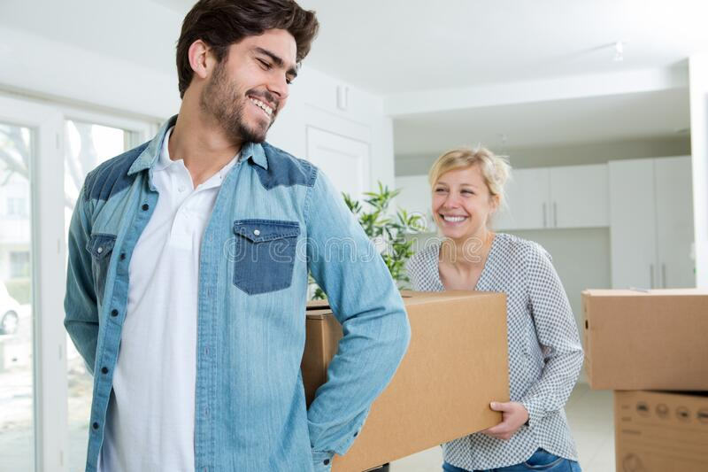 Happy young couple carrying box in apartment stock image
