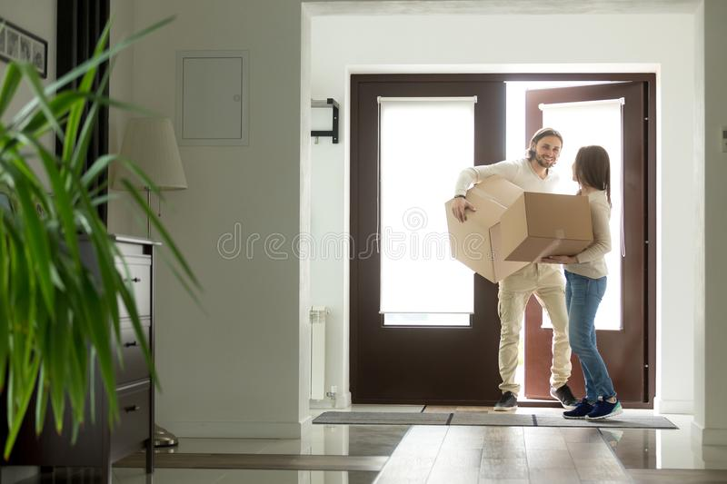 Couple carrying boxes entering house, homeowners moving in new h. Happy young couple carrying cardboard boxes opening door entering inside modern own house royalty free stock image
