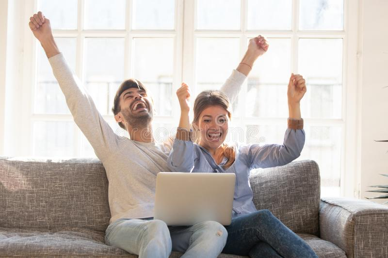 Happy young couple celebrate online victory, using laptop together stock images