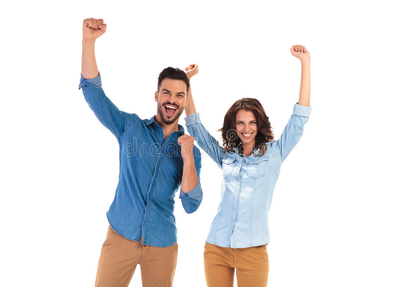 Happy young couple celebrating success with hands up. In the air on white background royalty free stock images