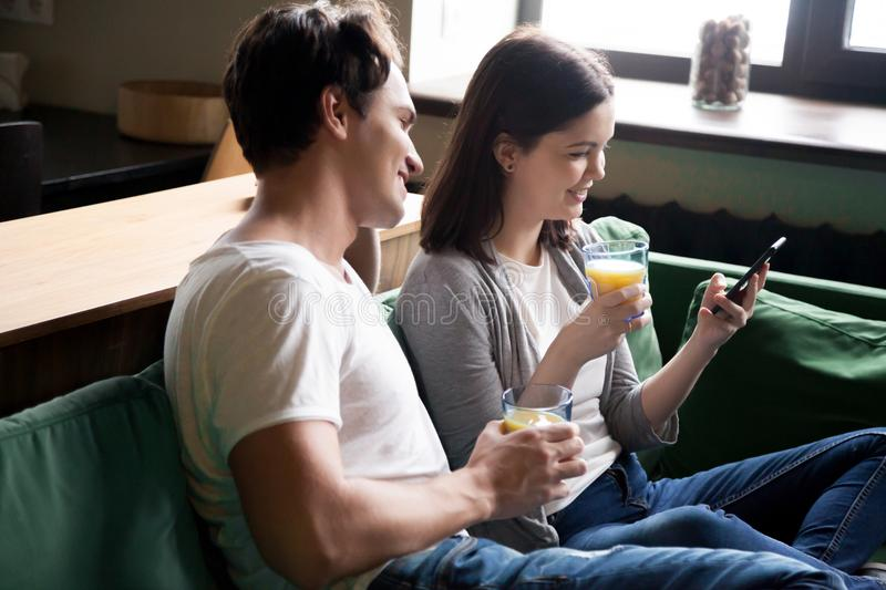 Happy young couple checking social networks news drinking orange royalty free stock photography