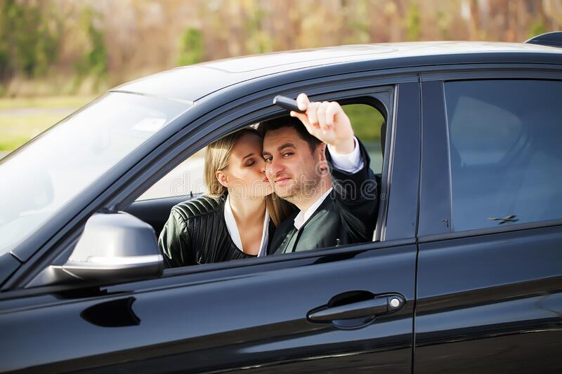 Happy young couple chooses and buying a new car for the family royalty free stock photos