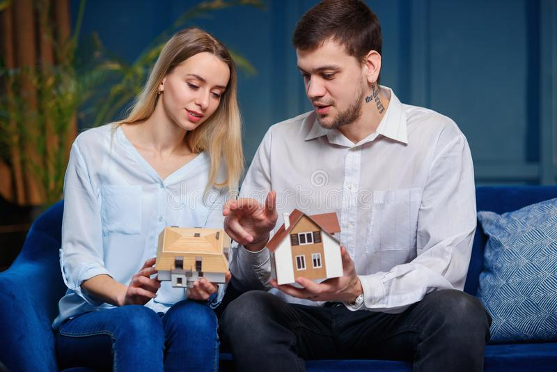 Happy young couple choosing the model of 3d maket of house. royalty free stock photography