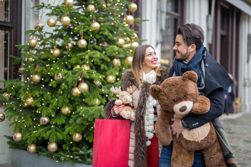 Happy young couple christmas shopping on the street. At daytime stock photos