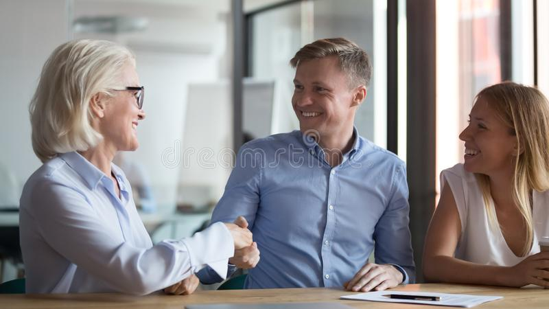 Happy young couple handshake broker making insurance investment bank deal. Happy young couple clients handshake old manager broker make insurance investment bank stock images