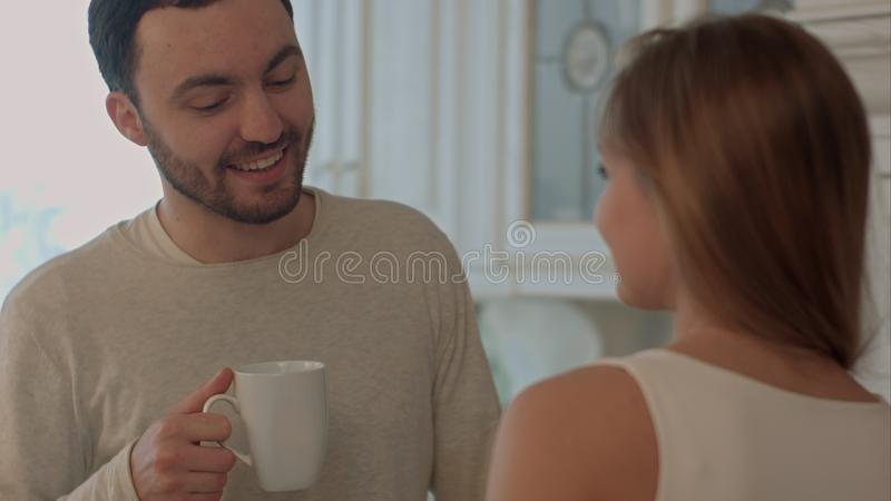 Happy young couple cooking together in the kitchen at home and kissing royalty free stock photo