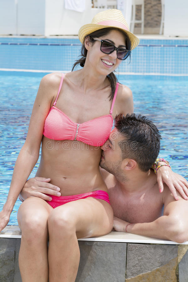 Happy young couple cuddling happy with love on the beach. Happy young couple on summer vacation smiling and hugging royalty free stock images