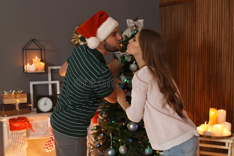 Happy young couple decorating Christmas tree together stock photo