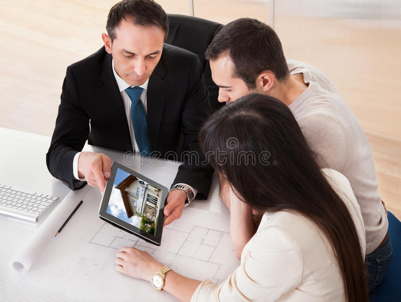 Happy Young Couple Discussing With Consultant stock photography