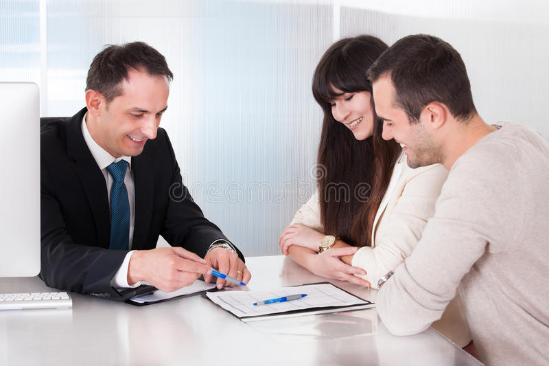 Happy young couple discussing with consultant. In Office royalty free stock photography