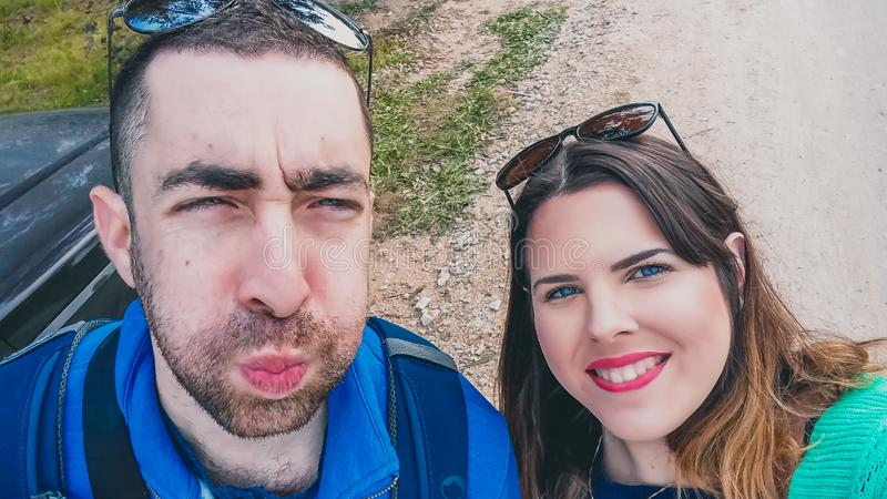 Happy young couple doing silly and funny faces while taking selfie picture with their smartphone or camera at the park.  stock photo