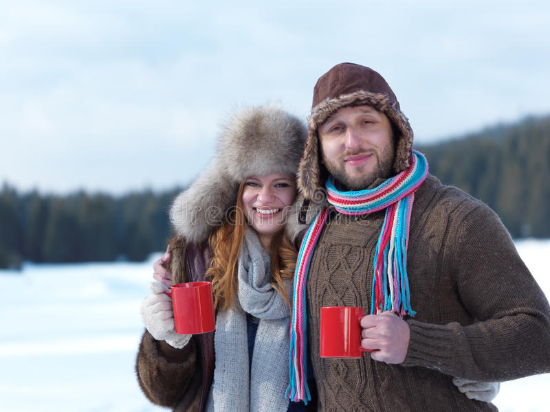 Happy young couple drink warm tea at winter. Portrait of happy young couple outdoor on winter day drinking warm tea with fresh snow in background royalty free stock photo