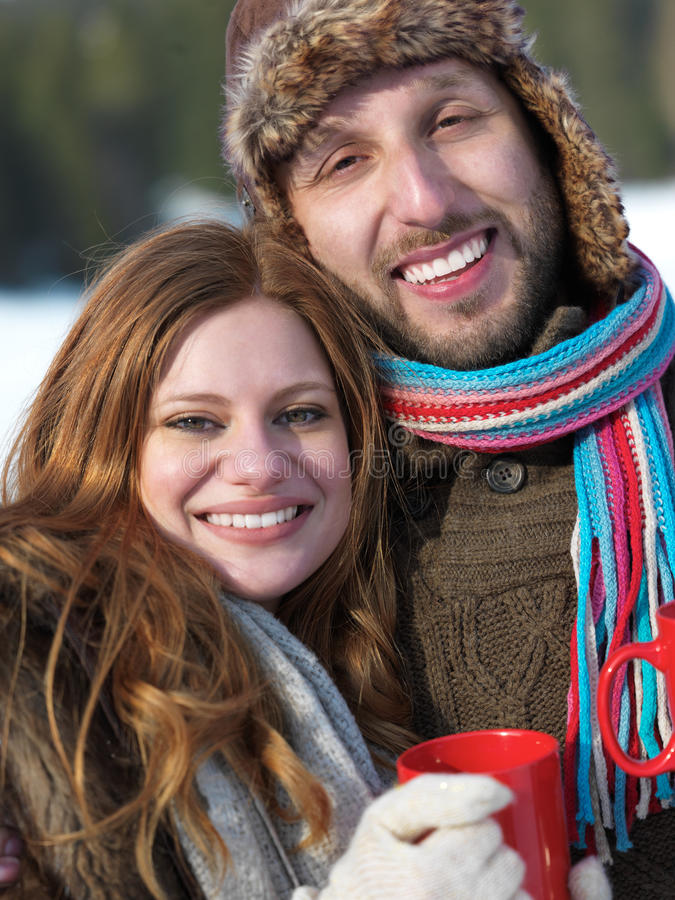 Happy young couple drink warm tea at winter. Portrait of happy young couple outdoor on winter day drinking warm tea with fresh snow in background stock photography