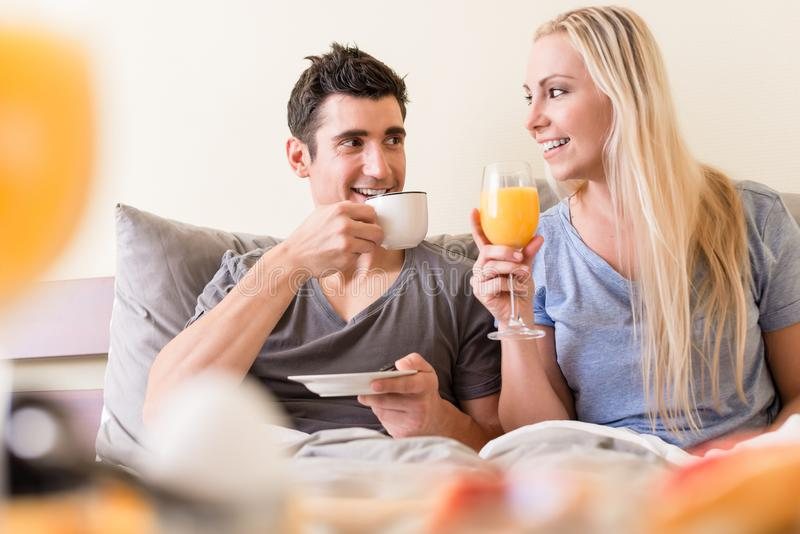 Happy young couple drinking coffee and orange juice royalty free stock photo