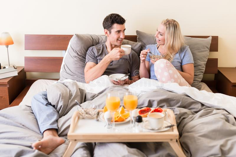 Happy young couple drinking coffee and orange juice. During relaxing breakfast in bed stock image