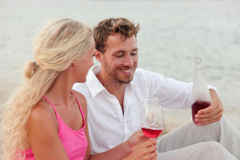 Happy Young Couple Drinking Red Wine Outdoors Beach royalty free stock images