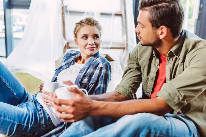 Couple drinking tea in new apartment stock image