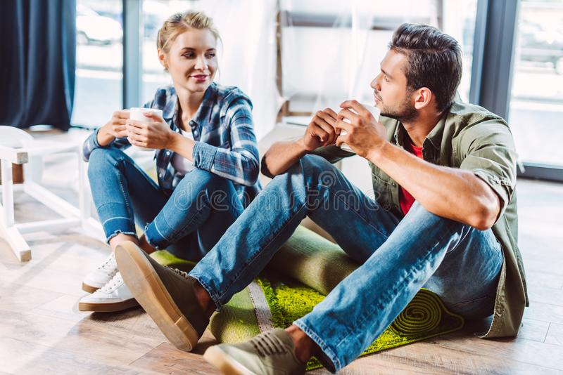 Couple drinking tea in new apartment stock photography