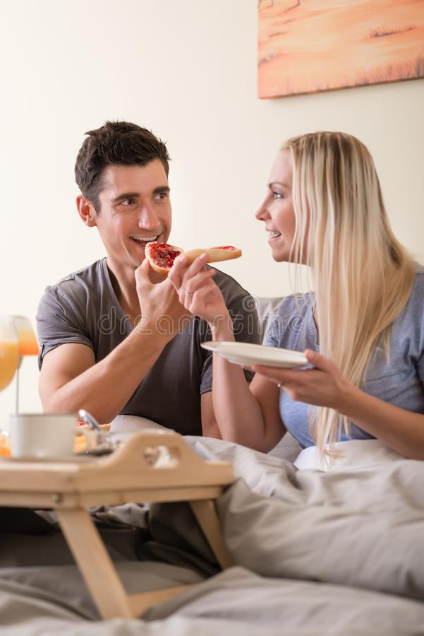 Happy young couple having breakfast in bed royalty free stock photography