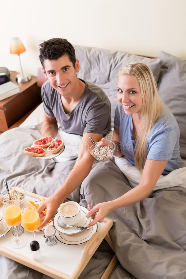 Happy young couple having breakfast in bed. Happy young couple eating bread and strawberry jam while having breakfast in bed royalty free stock image