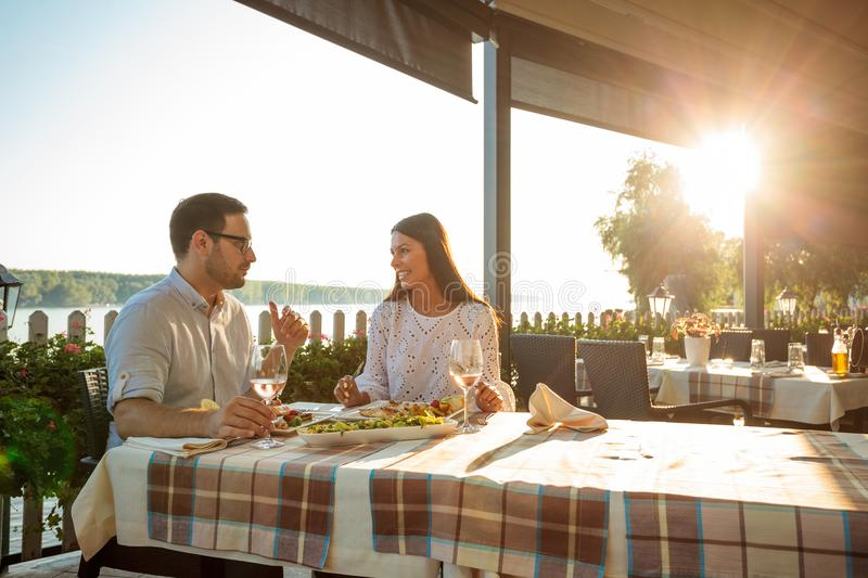 Happy young couple eating fish dinner and drinking wine in riverside restaurant stock photo