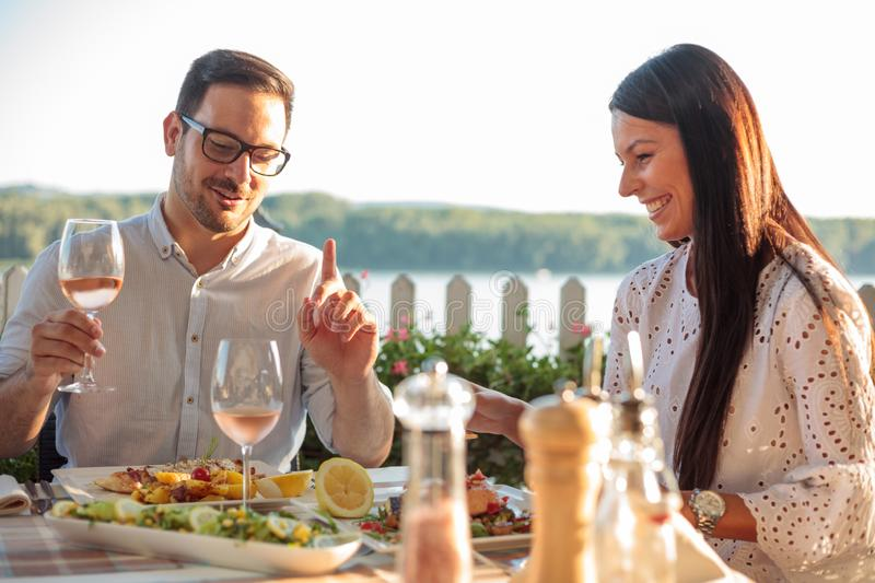 Happy young couple eating fish dinner in riverside restaurant royalty free stock photos
