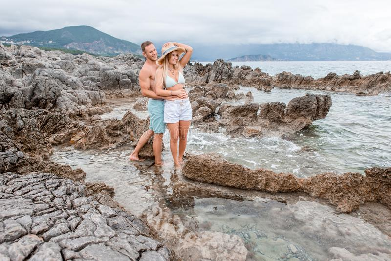happy young couple embracing and looking away while standing together on rocky beach stock images