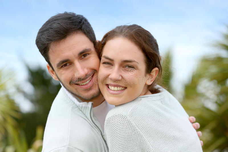 Happy young couple embracing outdoors. Couple embracing each other in front of house stock images