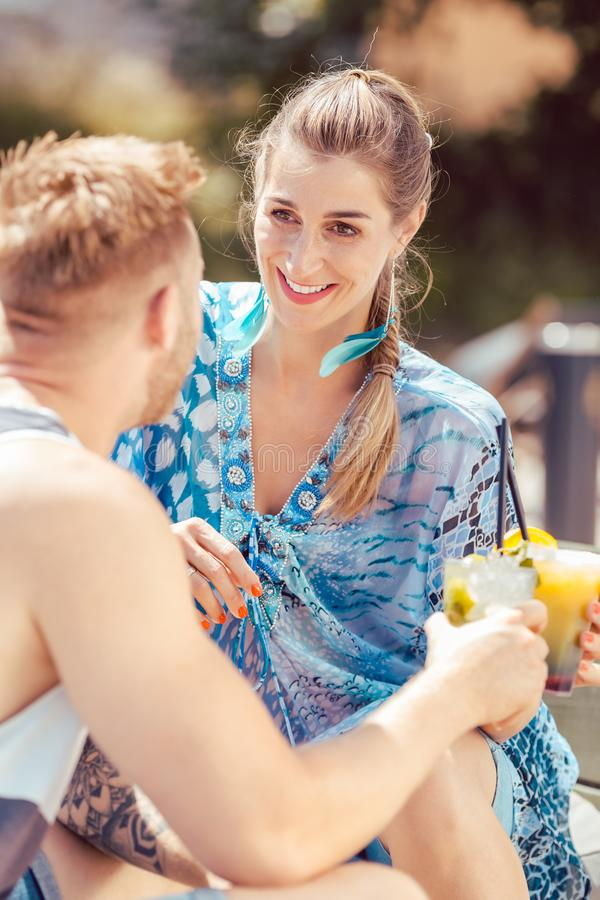 Happy young couple enjoying cocktails royalty free stock photo