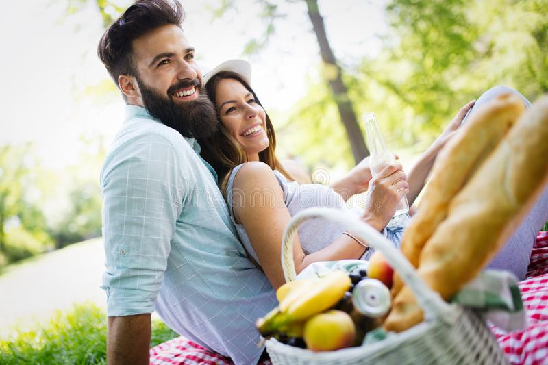 Happy young couple enjoying a picnic in the park together stock image
