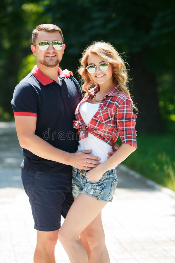 Happy young couple enjoying summer green park. An attractive young couple, men and women in sun glasses and shorts, spend a day in a city park, enjoying a warm royalty free stock photography