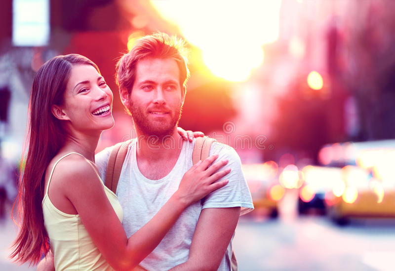 Happy young couple enjoying urban city lifestyle. Happy Asian woman, Caucasian men multiethnic couple relaxing in sunset laughing smiling on urban city street in royalty free stock photo