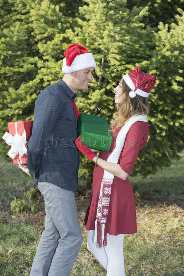 Happy young couple exchanging Christmas presents stock image