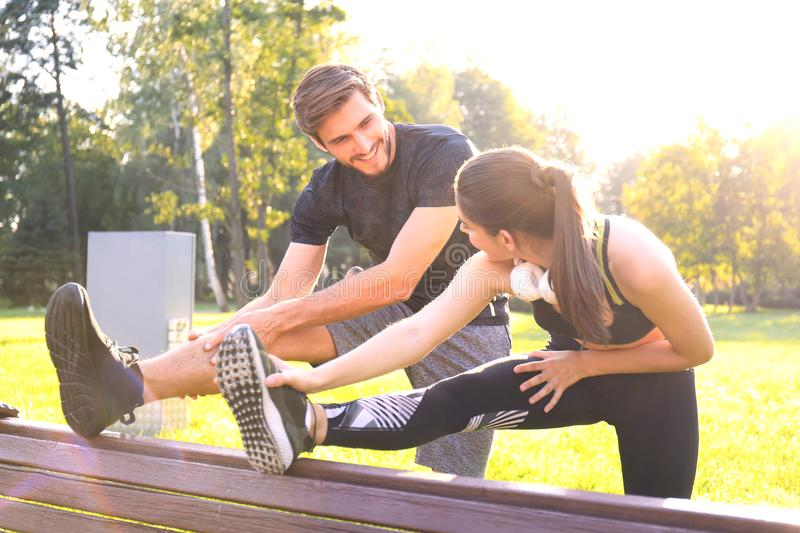 Happy young couple exercising together in a park, stretching exercises.  stock photo
