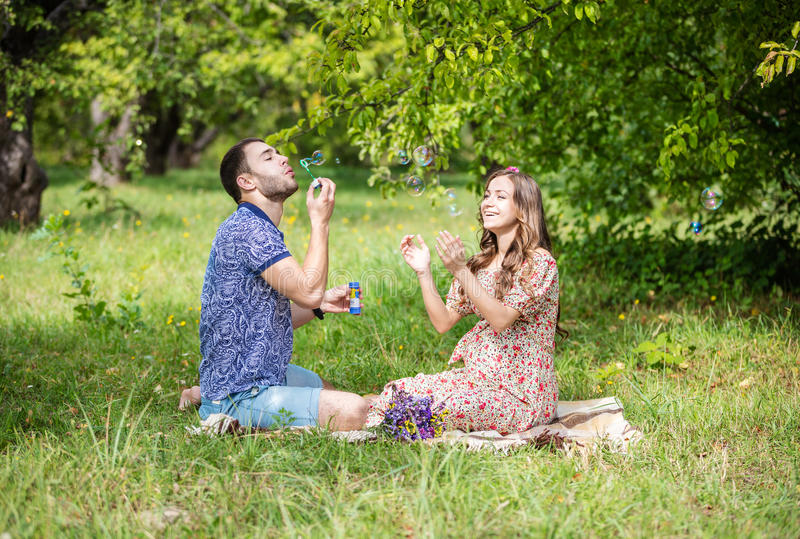 Happy young couple expecting baby, pregnant woman with husband blowing bubbles and laughing stock images