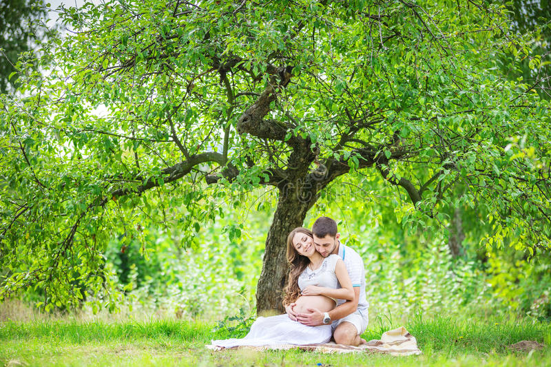 Happy young couple expecting baby, pregnant woman with husband touching belly royalty free stock photography