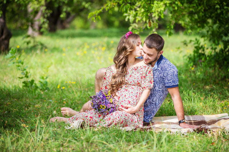 Happy young couple expecting baby, pregnant woman kissing her husband royalty free stock image