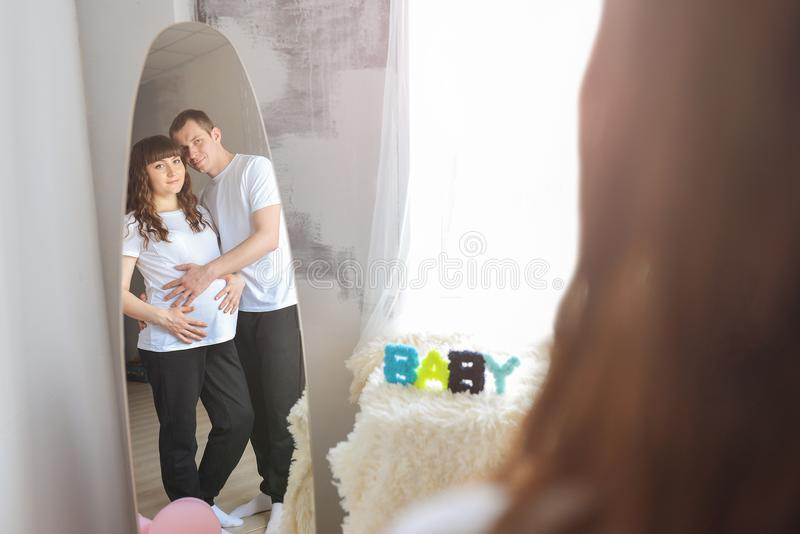Happy young couple expecting baby standing together embracing and looking at mirror. Man holding a belly of his pregnant royalty free stock photos