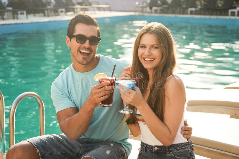 Happy young couple with fresh  cocktails relaxing near swimming pool royalty free stock images